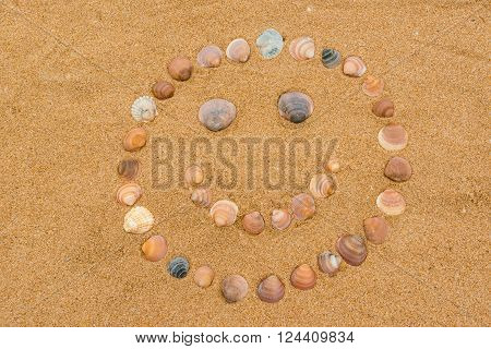 Happy face created on the sandy beach using individual seashells