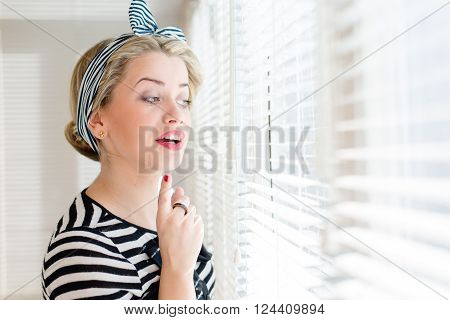 closeup picture of beautiful blond young woman pinup girl having fun happy smiling and looking excited through sun lighted windows