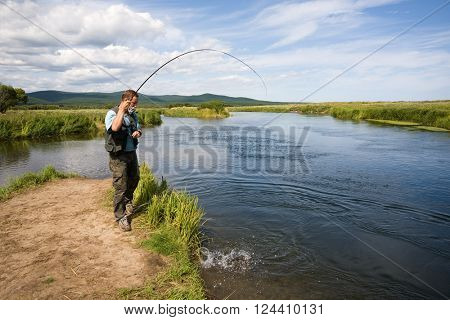 Man fishes caught salmon from the river. Far East Russia.