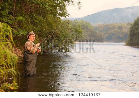 Fisherman on a mountain river catches of pink salmon. Far East Russia. Image retro vintage filter effect.