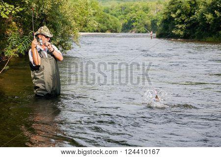 Joyful fisherman fishes salmon (pink salmon) on the mountain river. Far East Russia.