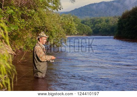 Joyful fisherman on a mountain river catches of salmon (pink salmon). Far East Russia.