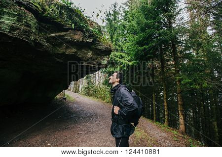 Young ManStudent hiking in forest.Man hiker smiling happy portrait looking up enjoying nature on foggy day during a trekking trip. Back of a young man outdoors in nature on a hiker path in forest.