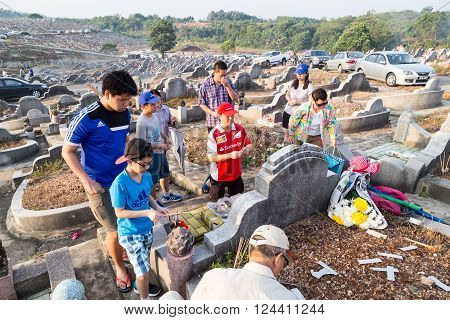 KUALA LUMPUR MALAYSIA April 2 2016: Chinese descendants cleaning tomb and offering prayers to ancestors during the annual QingMing or tomb sweeping day at cemetery in Malaysia