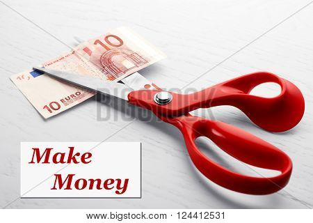 Concept of spending money - scissors cut money