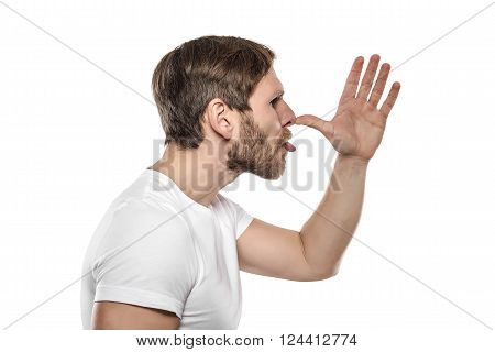 Man in white T-shirt tease someone and grimaces. Isolated over white