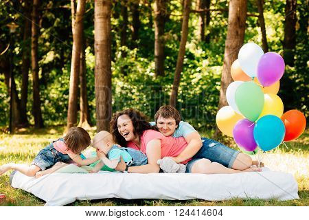 Young family with kids having fun with pillows and colored balloons outdoors. Parents with two children relax in a sunny summer garden. Mother father little girl and baby boy playing in park.