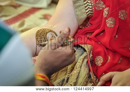 Mehndi artist applying henna on bride's hand called mehendi ceremony