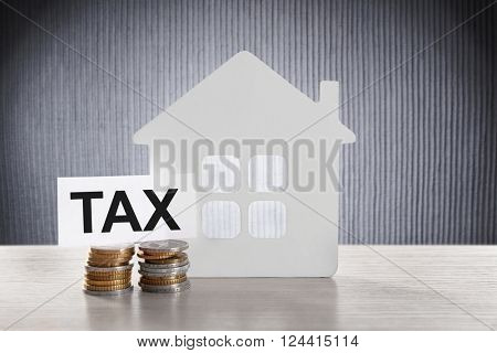 House figure, coins and tax sign on grey background