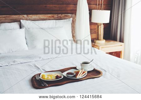 Breakfast on a tray in bed in hotel, white linen, wooden interior