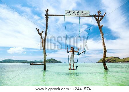 Girl swinging at tropical beach, sunny day, good weather. Swinging in paradise island.