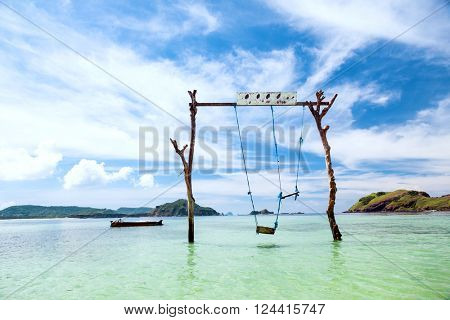Swings in paradise island at tropical beach, sunny day, good weather.