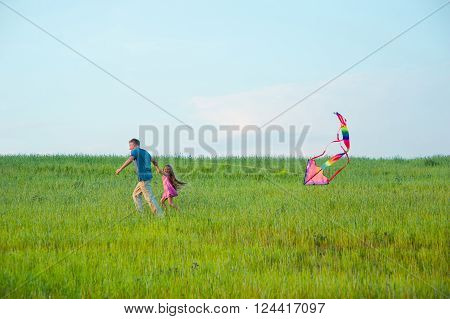 Dad and daughter fly a kite on a green grass. Father spending time with his daughter.