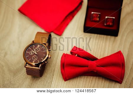 Groom's morning. Wedding accessories in red colors. Tie-butterfly cufflinks watch handkerchief.