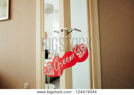 Groom sign hanging on the opened door. Groom on the background