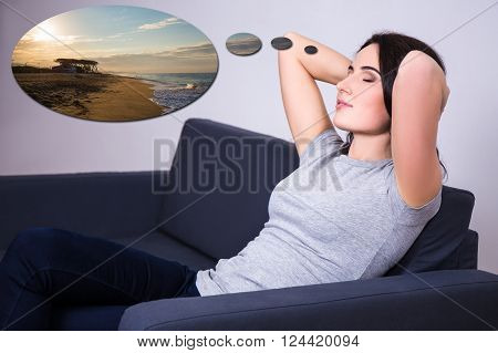 Young Woman Lying On Sofa At Home And Dreaming About Summer