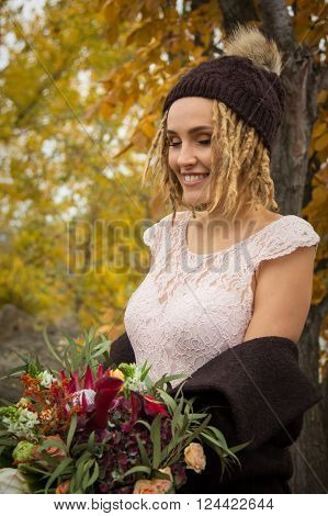 Beautiful blonde woman with a dreadlocks hairstyle in coat and knitted cap