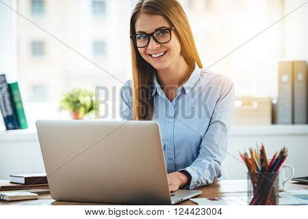 Elegant and cheerful businesswoman. Cheerful young beautiful woman in glasses looking at camera with smile while sitting at her working place