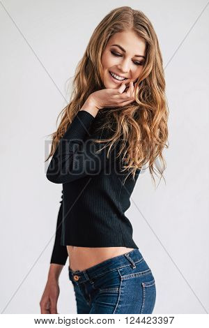 Flirty and gorgeous. Beautiful young woman posing and looking down with smile while standing against white background