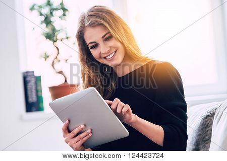 Surfing net at home. Beautiful young woman using digital tablet with smile while sitting on sofa at home