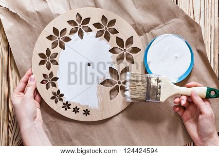 Master Class. Watch handmade. Step by step instructions for the manufacture of clocks. Kraft paper on a wooden background. Do it yourself. Hands with paint brush watch white acrylic paint.