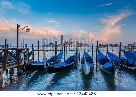 Gondolas moored by Saint Mark square with San Giorgio di Maggiore church in the background in the evening, Venice, Italia