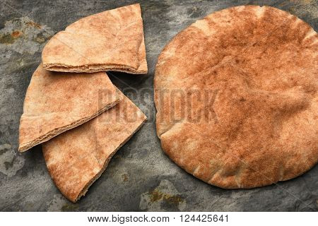 Top view of a loaf of Pita bread and three pita wedges on a slate table.