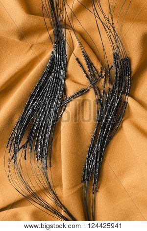 Strings of black glass beads on yellow draped silk as a background