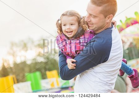 Father holding daughter in his arms having fun at the fun fair, amusement park ** Note: Soft Focus at 100%, best at smaller sizes