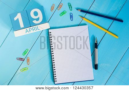 April 19th. Image of april 19 wooden color calendar on blue background.  Spring day, empty space for text. The Day of Snowdrop.
