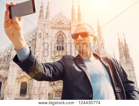 Man take a selfie photo on Duomo di Milano background