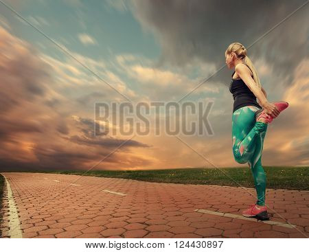 Blonde girl prepares to start running warming up