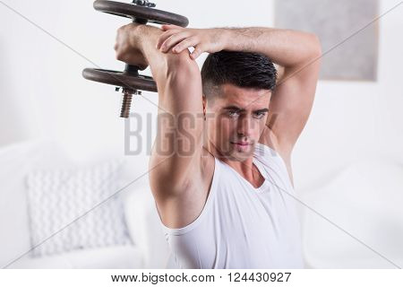 Fit young man strengthening arm muscles with dumbbell