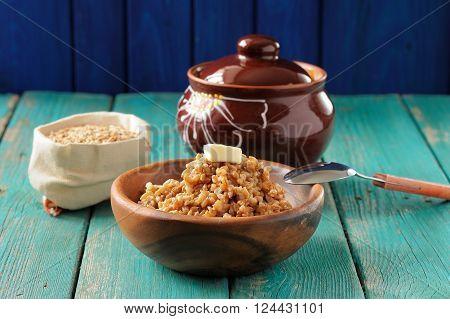Spelt porridge buttered in wooden bowl and raw spelt in linen bag on wooden table