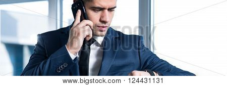 Young handsome busy businessman talking the phone with important client. Leading transaction by mobile phoneYoung handsome busy businessman talking the phone with important client. Leading transaction by mobile phone