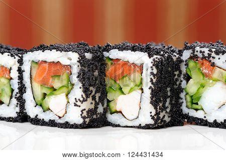Japan square black tobiko rolls with shrimp salmon and cucumber copyspace closeup