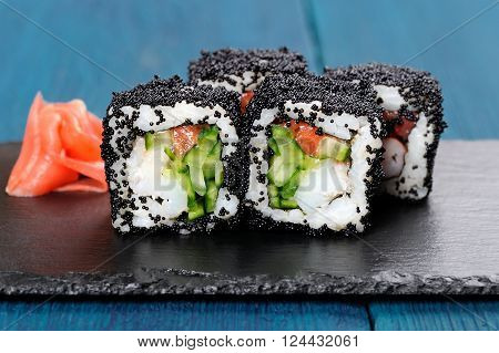 Japan black tobiko rolls with cream cheese and cucumber served with ginger on black board closeup