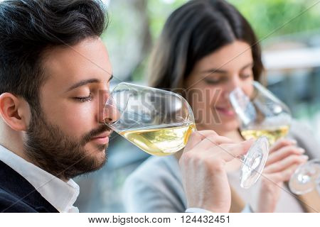 Close up portrait of young couple tasting white wine tasting.