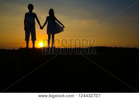 Silhouettes of children against a decline on a glade