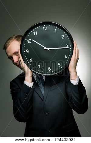 Young businessman in suit holding big clock. Living in permanent haste
