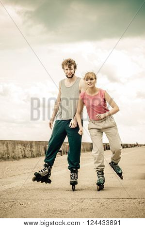 Hobby and spending free time in summer. Sport and exercising. Healthy body and wellbeing. Couple have fun together rollerblading outdoors.