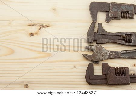 Old rusty mechanics tools on a wooden background. Advertising for new tools. Sales tools. Place for your text.