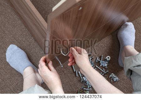 Woodworker assembling furniture at home using hex wrench, allen key.