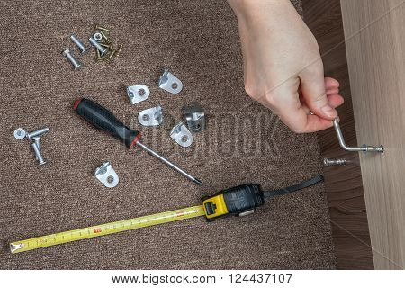 Assembling wood furniture used Hex wrench Allen Key human hand makes screwed furniture screw.
