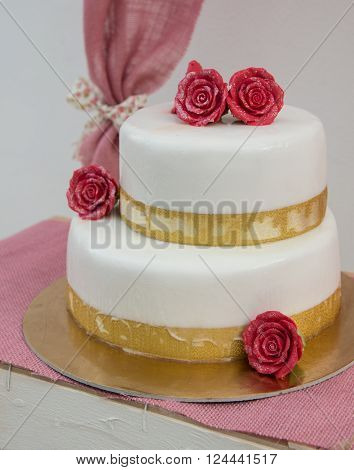 Birthday cake covered with sugar and decorated with sugary roses.
