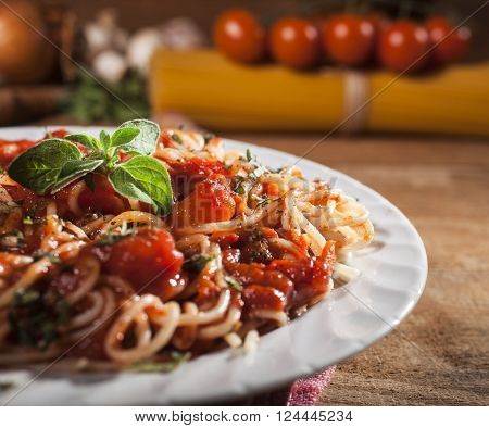 Spaghetti pasta with meatballs and tomato sauce on wooden background