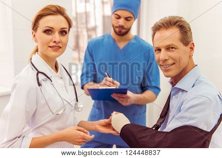 Beautiful female doctor in white gown is examining patient's hand in cast in the background a male doctor is taking notes