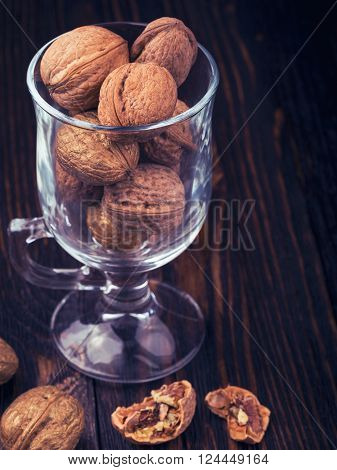 Walnut kernels and whole walnuts in a glass on a dark old wooden table