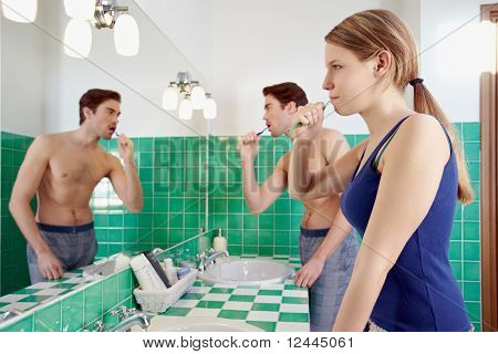 Husband And Wife Brushing Teeth In Bathroom