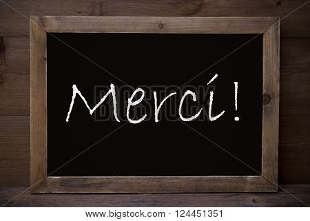 Brown Blackboard With French Text Merci Means Thank You As Greeting Card. Wooden Background. Vintage Rustic Style.